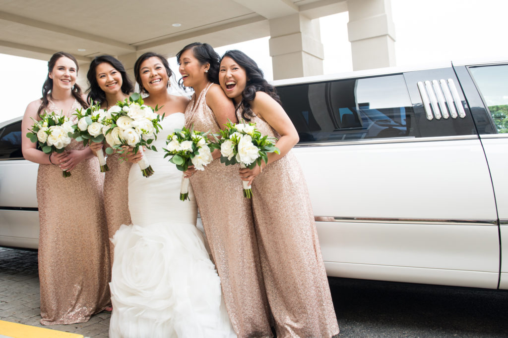 bridesmaids laughing in front of limo