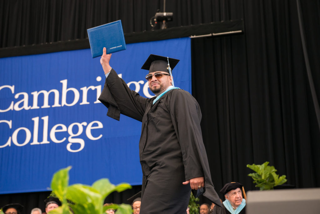 Bob Rivers Cambridge College Commencement graduate shows diploma