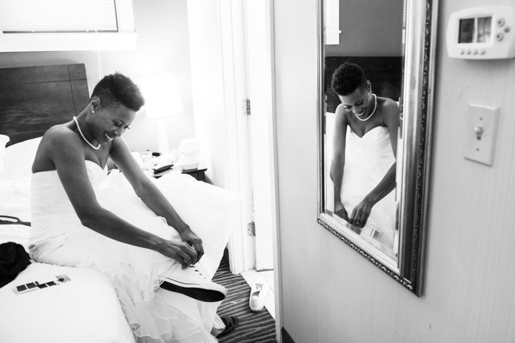 bride puts on sneakers before her wedding ceremony