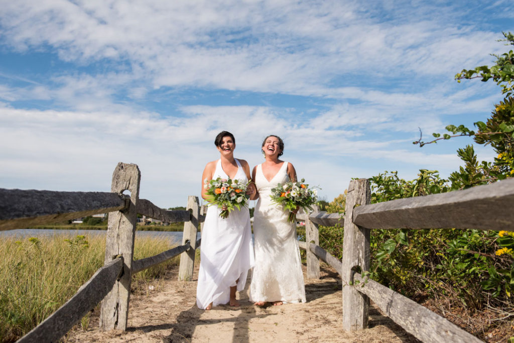 two brides walking and laughing on the beach cape cod massachusetts