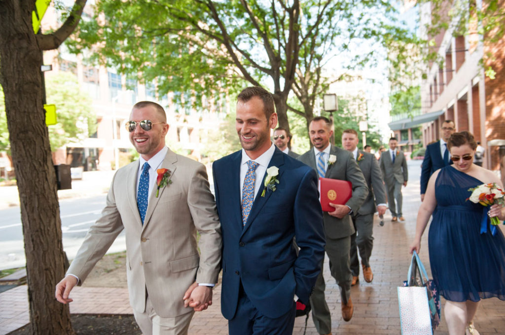 two grooms walk hand in hand to their wedding
