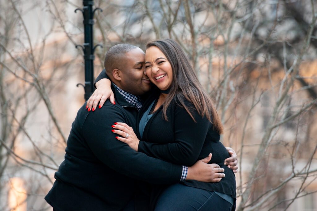 engagement photo at Boston College. couple is embracing; one person is saying something and the other person is laughing with their eyes closed