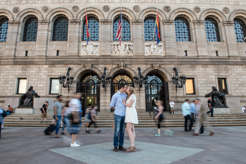 boston engagement photo where couple stands together in front of Boston Public Library and a crowd seems to rush around them. they are still and everyone else is in motion blur