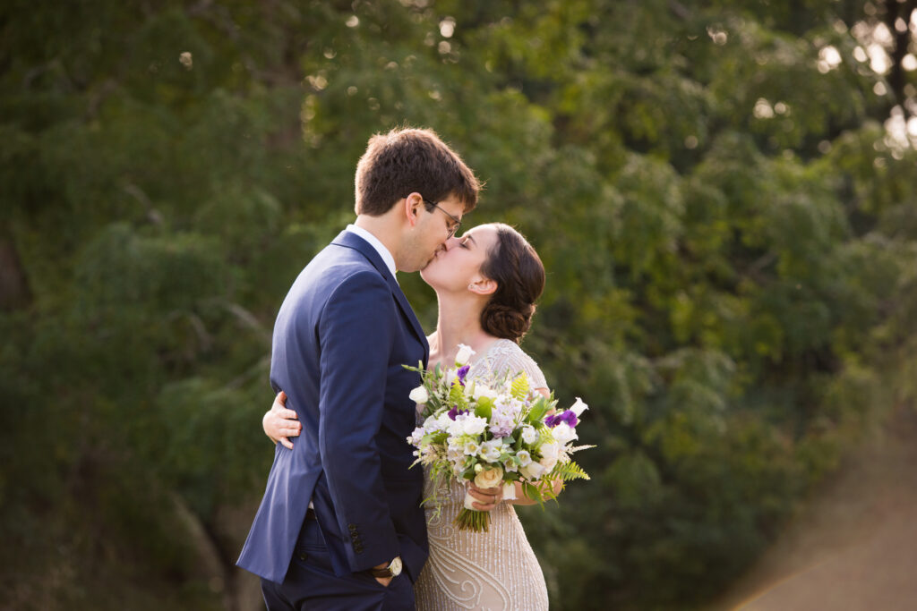 codman estate wedding photo couple kissing in front of greenery