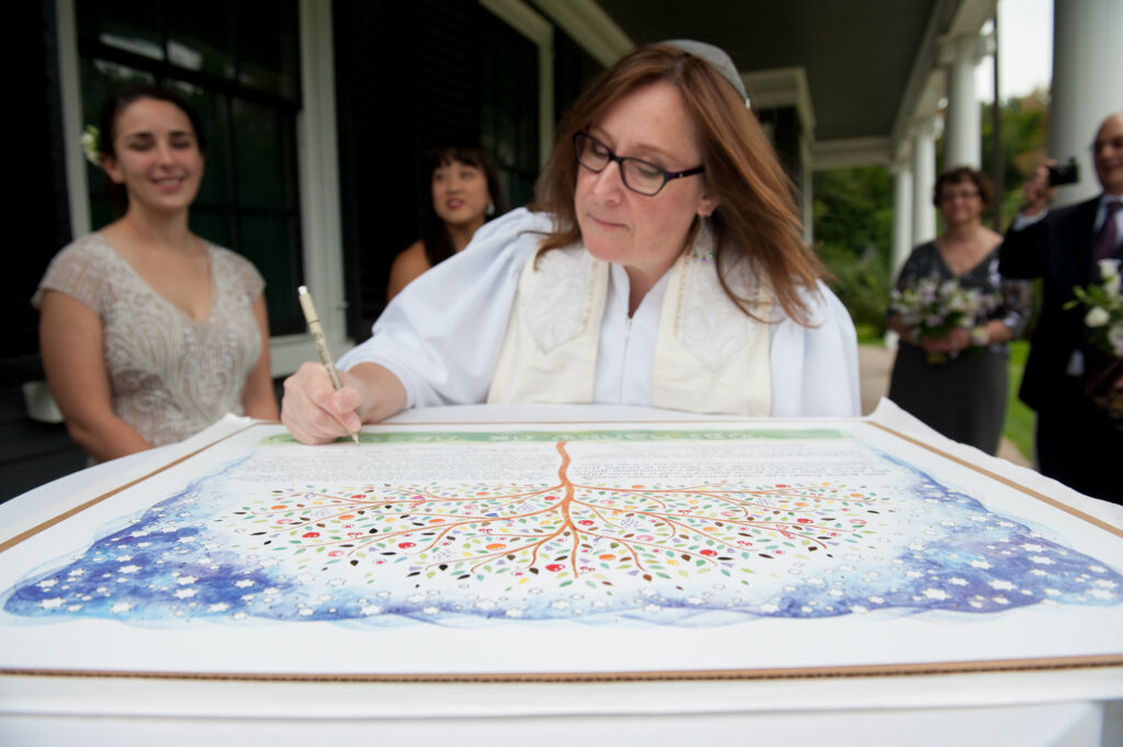codman estate wedding photo rabbi signs a ketubah jewish wedding contract