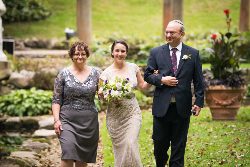 codman estate wedding bride walks down the aisle with her parents on each side