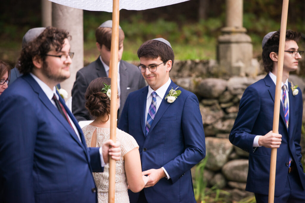 codman estate wedding couple stands under a chuppah holding hands