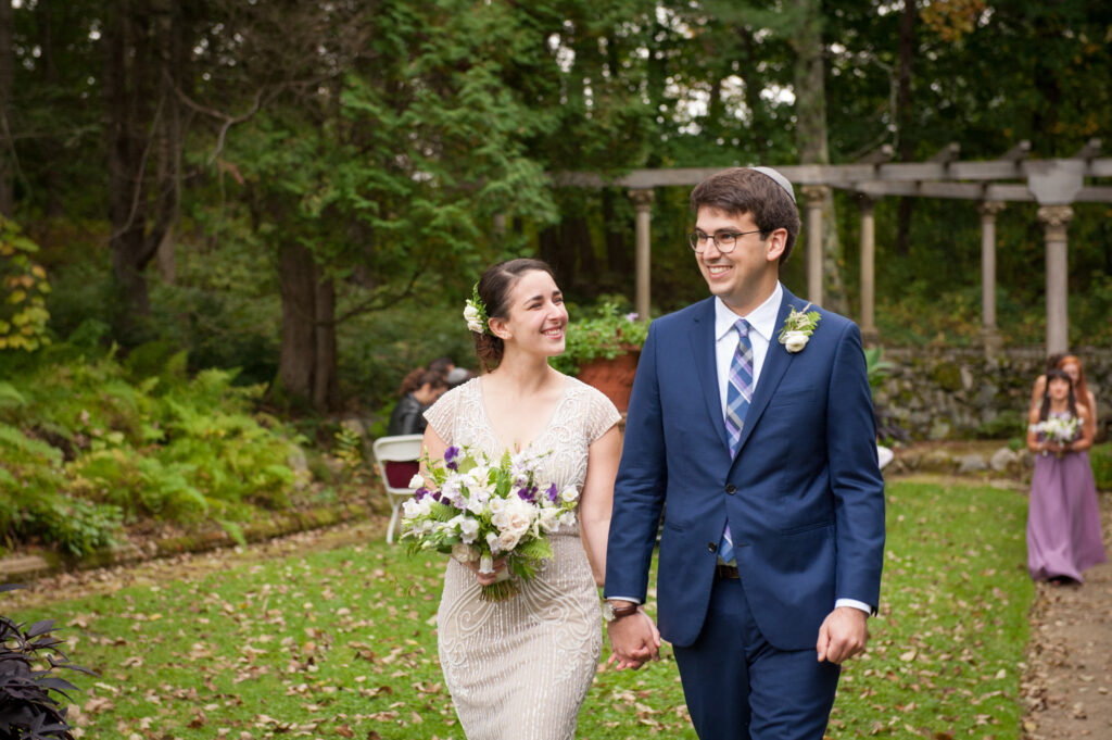 codman estate wedding couple walking away from ceremony site holding hands and smiling