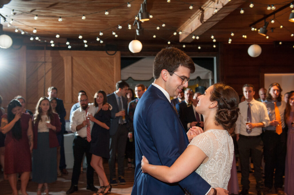 codman estate wedding couple first dance inside carriage house with friends looking on