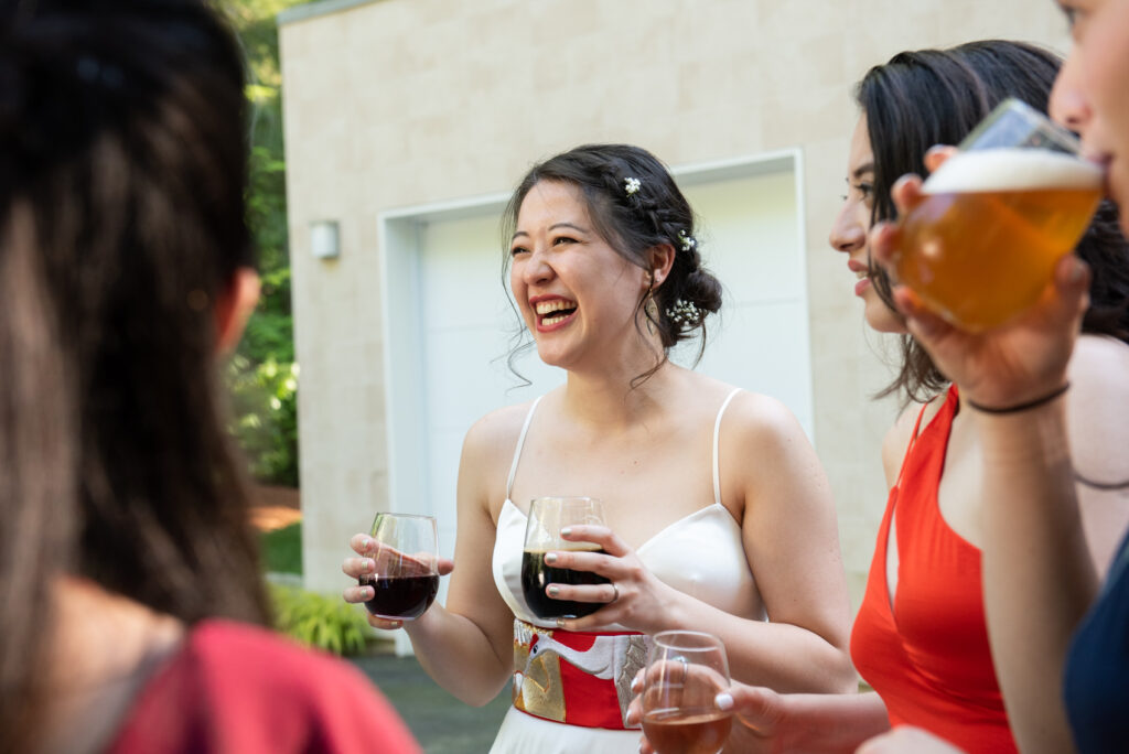 woman laughs candidly with her friends during her wedding reception at a backyard wedding in Lexington, Massachusetts