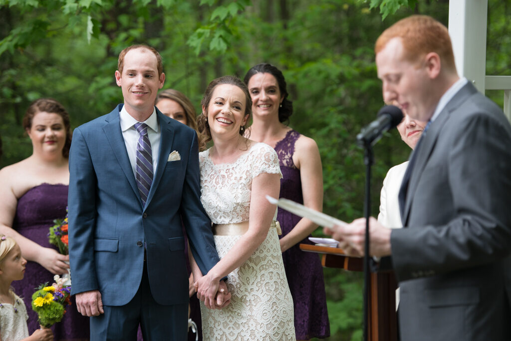 marrying couple smile as they listen to a reading during their outdoor ceremony in New Hampshire