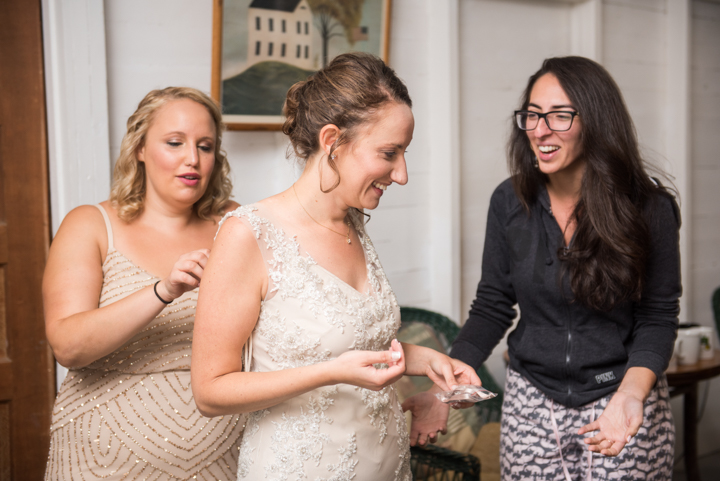 woman gets ready for her wedding laughing and surrounded by friends