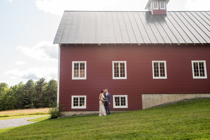 couple pose for a photo in front of a red barn before a fall wedding in Vermont