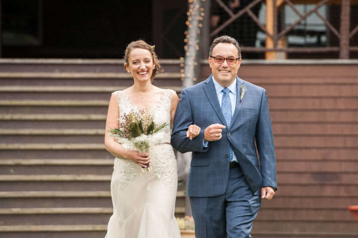 bride walks down the aisle with her father to an outdoor wedding ceremony in Vermont