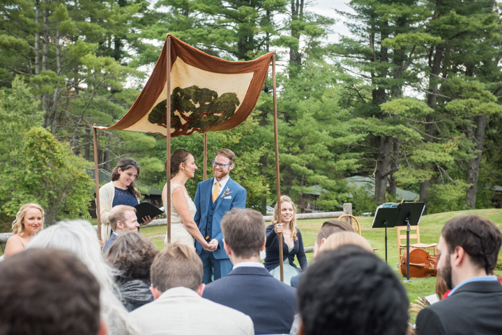 bride and groom stand under a Chuppah during their outdoor wedding ceremony