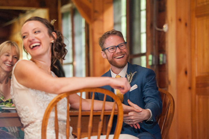 the marrying couple laugh while listening to a toast at their wedding