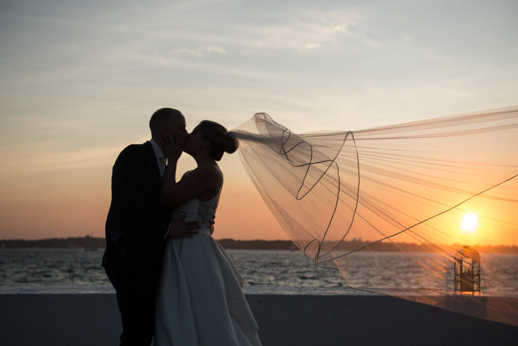 bride and groom kissin in sunset veil blowing in wind