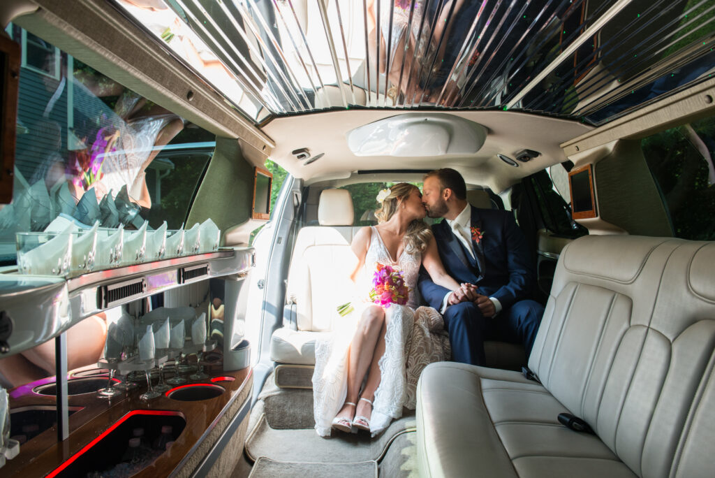 bride and groom kiss in a mirrored limo