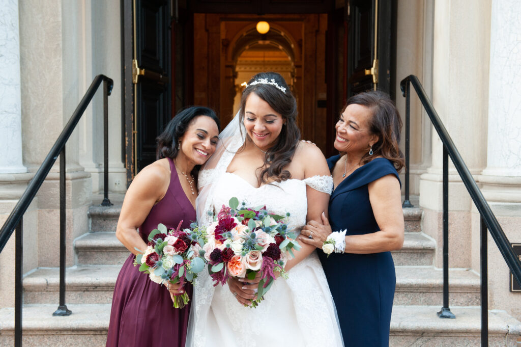 bride outside church with sister and mother