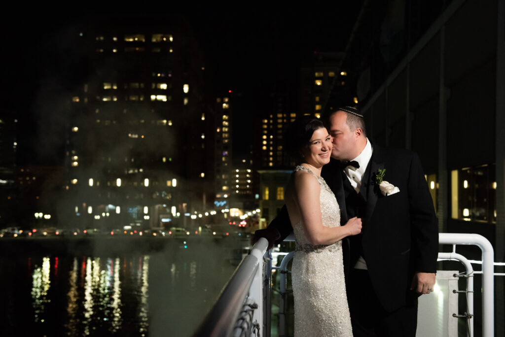 bride and groom kissing outside boston lights