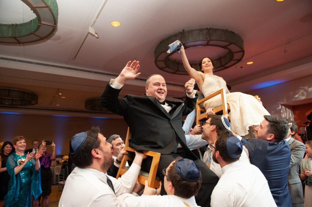 bride and groom lifted in chairs during Hora dance Jewish wedding Boston