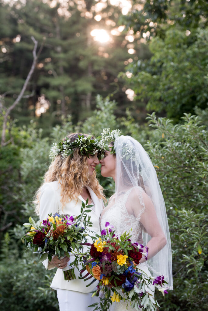 two brides kissing in sunlight with lots of flowers and greenery